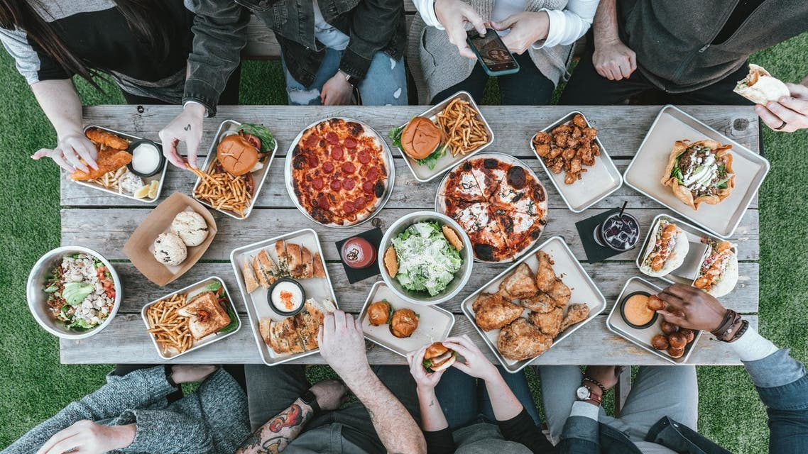 People sitting at a table with food on the grass. (Unsplash, Spencer Davis)