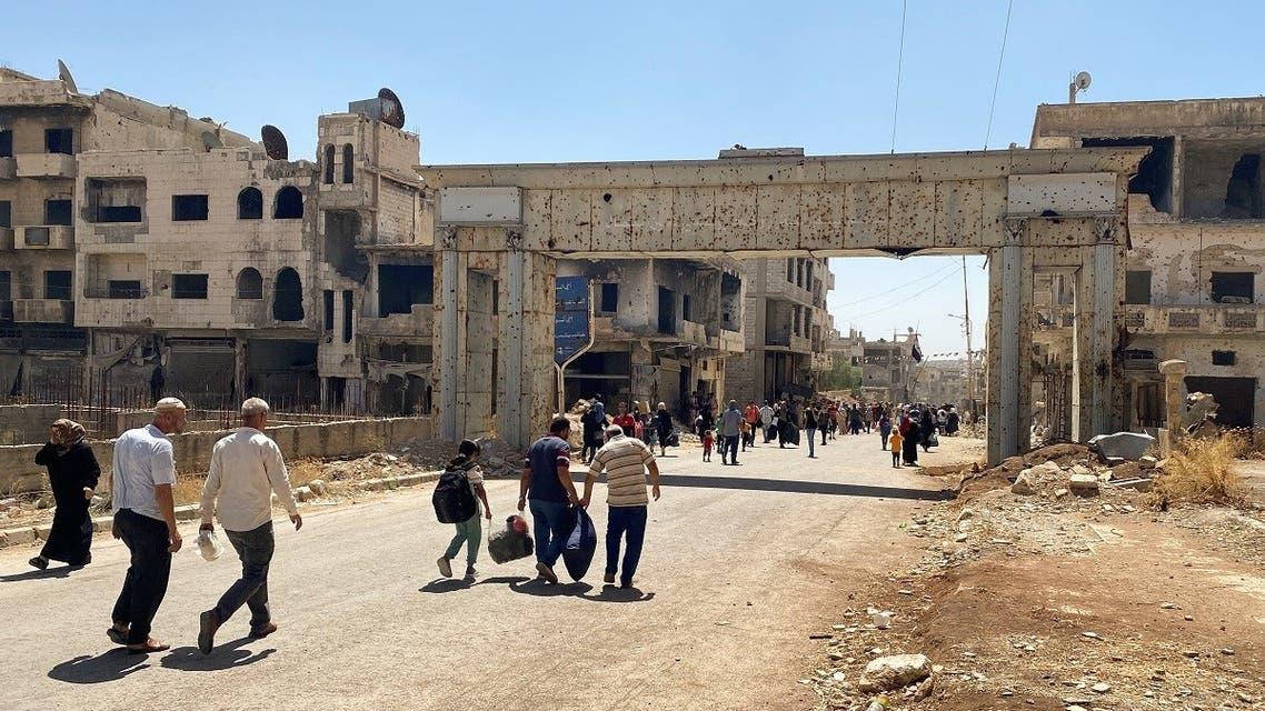 Residents hold their belongings as they return to their neighborhood in Deraa al Balaad, Syria, September 9, 2021. (Reuters)