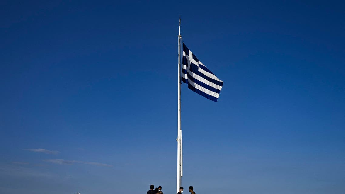 Tourists stand under a Greek flag on the Acropolis hill in Athens on June 8, 2021. (AFP)