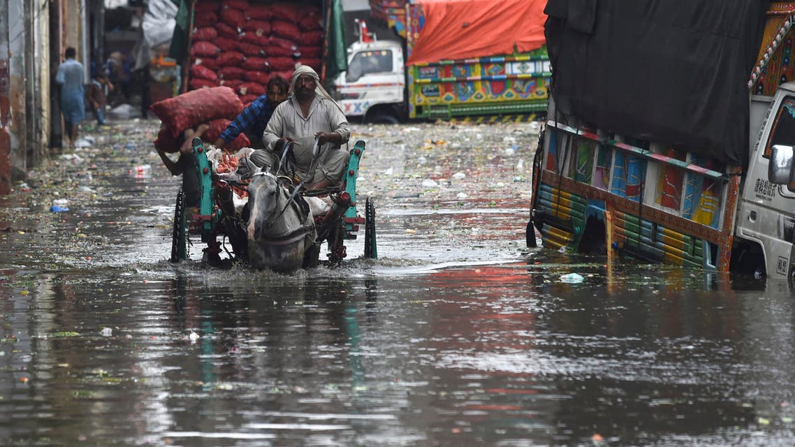 Men ride on a horsecart along a flooded street after a heavy downpour in Lahore on September 11, 2021. (AFP)