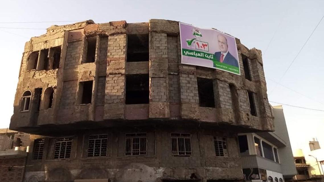 صورة أحد المرشحين على بناية مهدمة إثر المعارك مع داعش