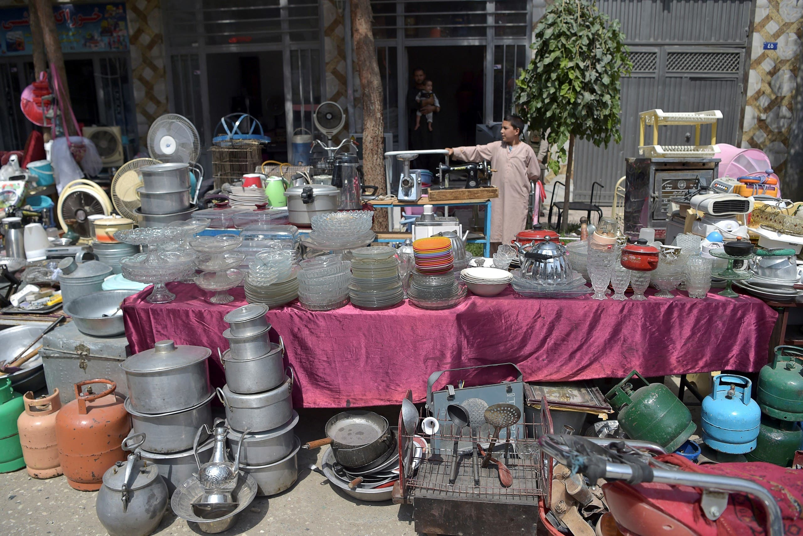 This photo taken on September 12, 2021 shows a young shopkeeper gesturing as he offers secondhand household items for sale at a market in the northwest neighbourhood of Khair Khana in Kabul. (AFP)