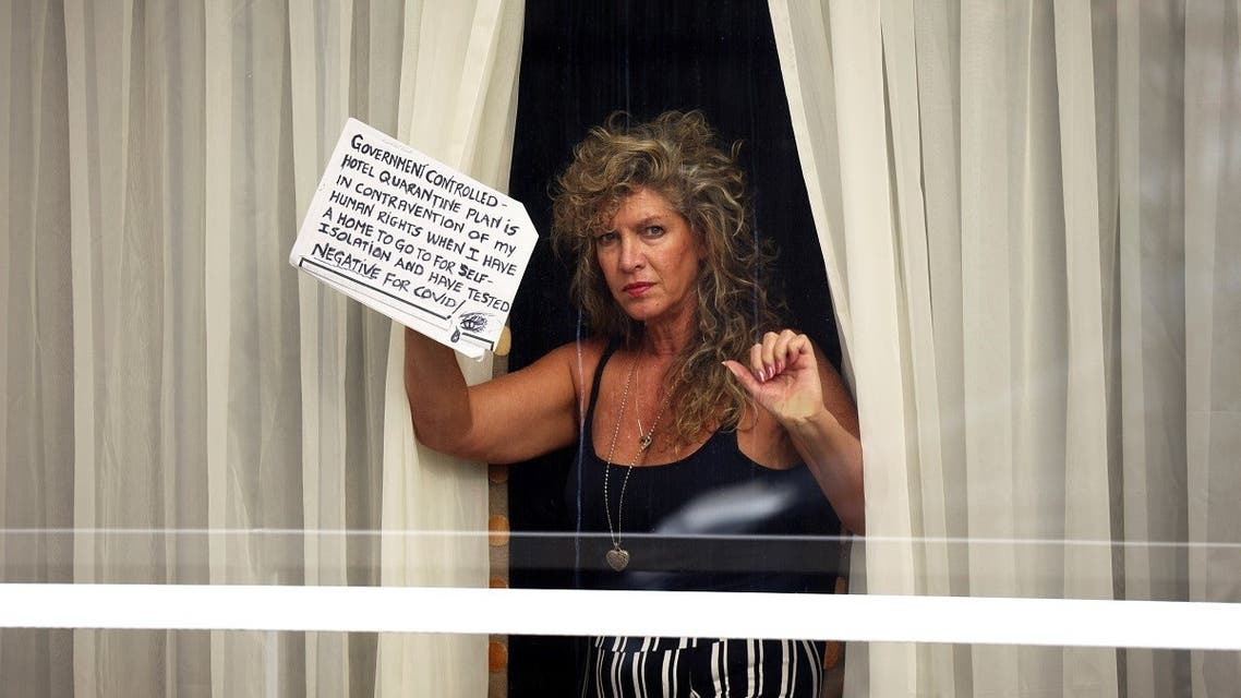 A woman holds a sign at a window of the Radisson Blu Hotel at Heathrow Airport, as Britain introduces a hotel quarantine programme for arrivals from a red list of 30 countries due to the coronavirus disease (COVID-19) pandemic, in London, Britain. (Reuters)