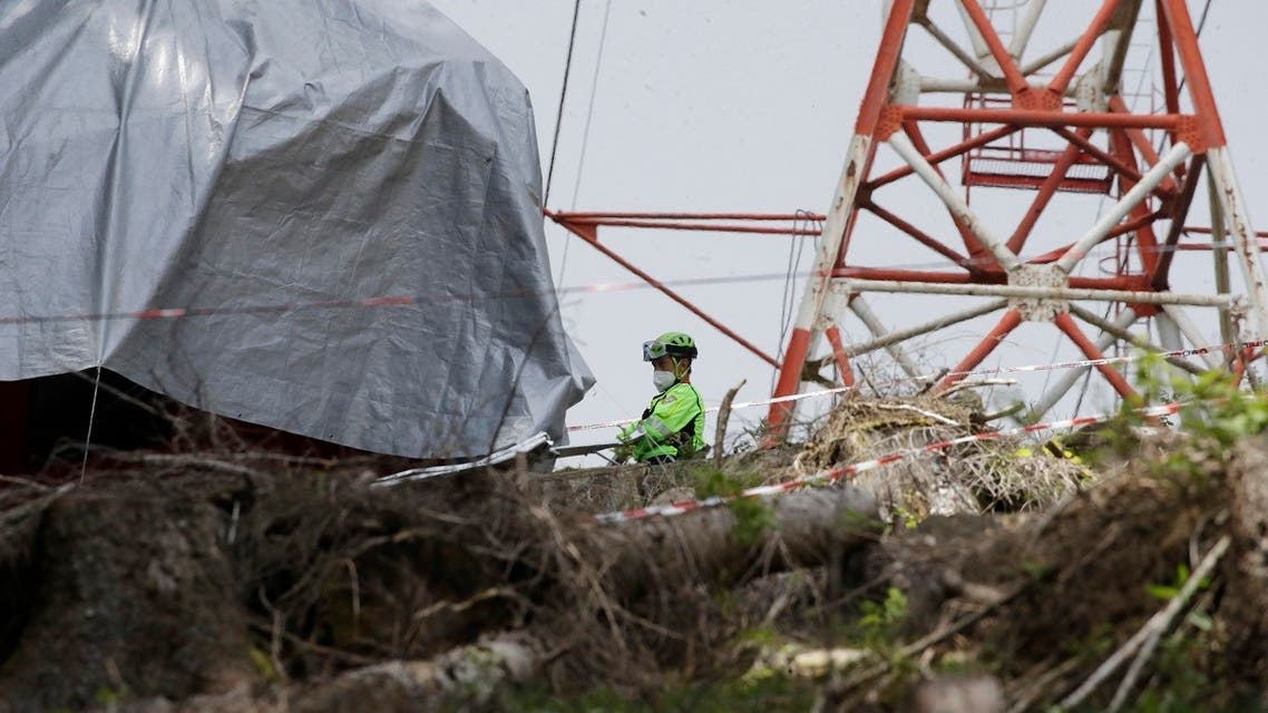 Rescuers search for evidence in the wreckage of a cable car after it collapsed near the summit of the Stresa-Mottarone line in the Piedmont region, northern Italy, Wednesday, May 26, 2021.  (AP)