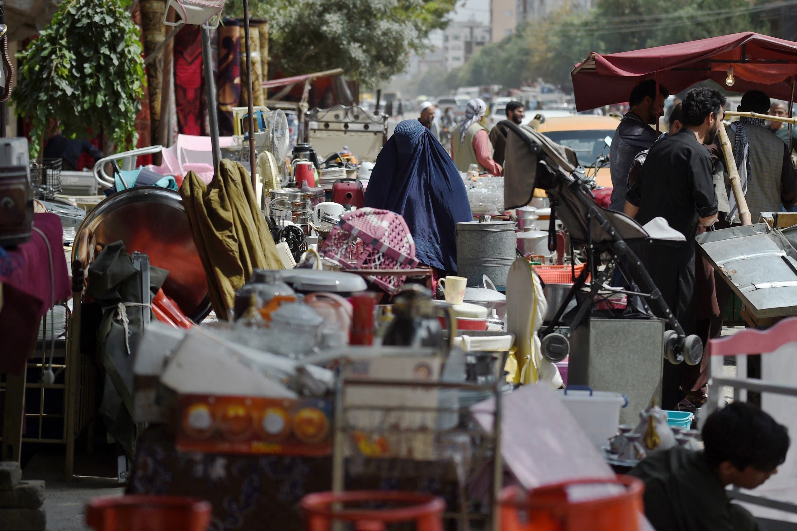 This photo taken on September 12, 2021 shows a woman looking at secondhand household items for sale at a market in the northwest neighbourhood of Khair Khana in Kabul. (AFP)