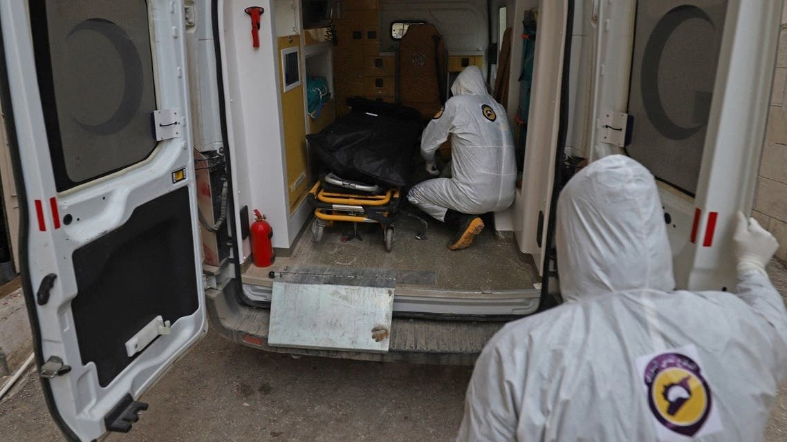 Members of Syrian Civil Defense, also known as the White Helmets, transport the body of a man who died from the coronavirus for burial in Syria's Idlib on November 19, 2020. (Abdulaziz Ketaz/AFP)