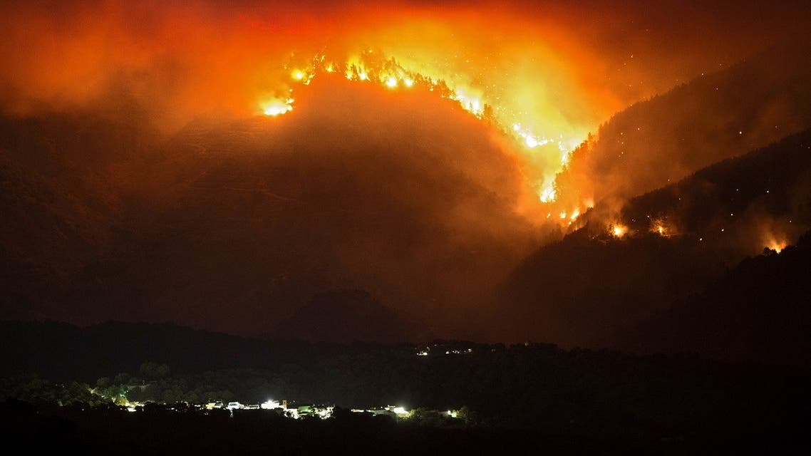 A picture taken from the village of Atajate shows the flames of a wildfire, that broke out three days ago, burning a forest area behind the village of Alpandeire on September 12, 2021. (Jorge Guerrero/AFP)