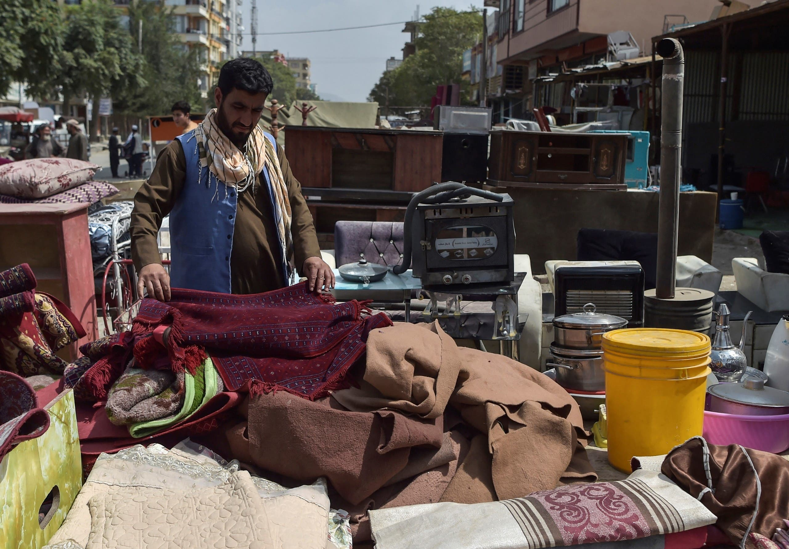 This photo taken on September 12, 2021 shows a man looking at secondhand household items for sale at a market in the northwest neighbourhood of Khair Khana in Kabul. (AFP)