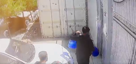 Security footage of aid worker Zemari Ahmadi loading water containers into his truck on the day that he was struck by a US military drone after being suspected of loading an ISIS bomb into his vehicle in Kabul, Afghanistan. (Screengrab)