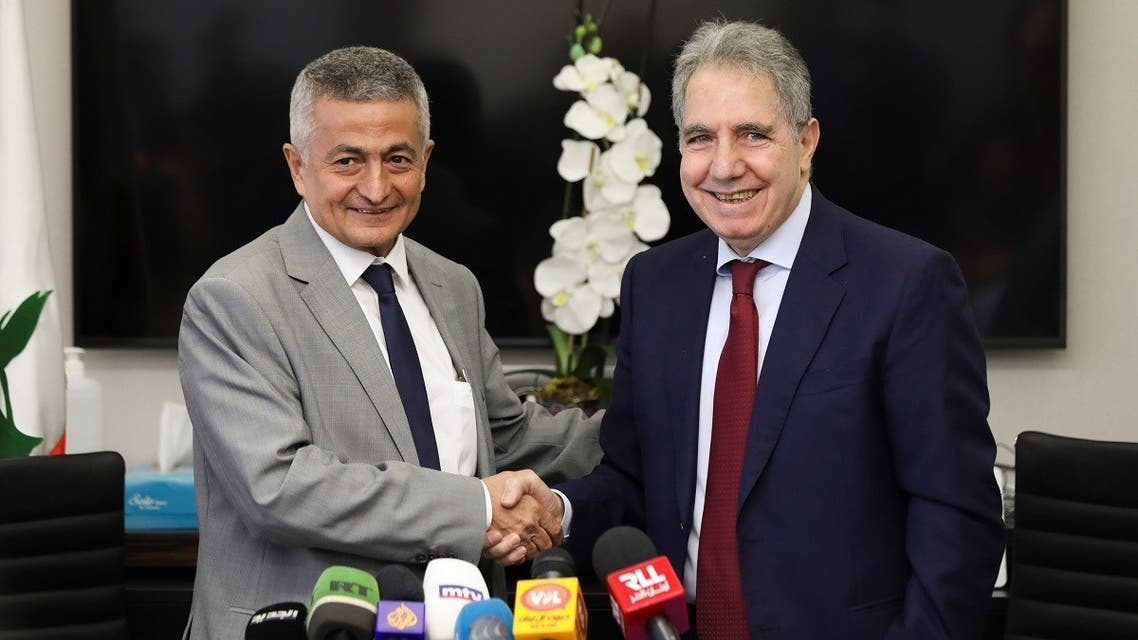 Lebanon's outgoing Finance Minister Ghazi Wazni shakes hands with the newly appointed Finance Minister Youssef Khalil during a handover ceremony in Beirut, Lebanon September 14, 2021. (Reuters/Mohamed Azakir)