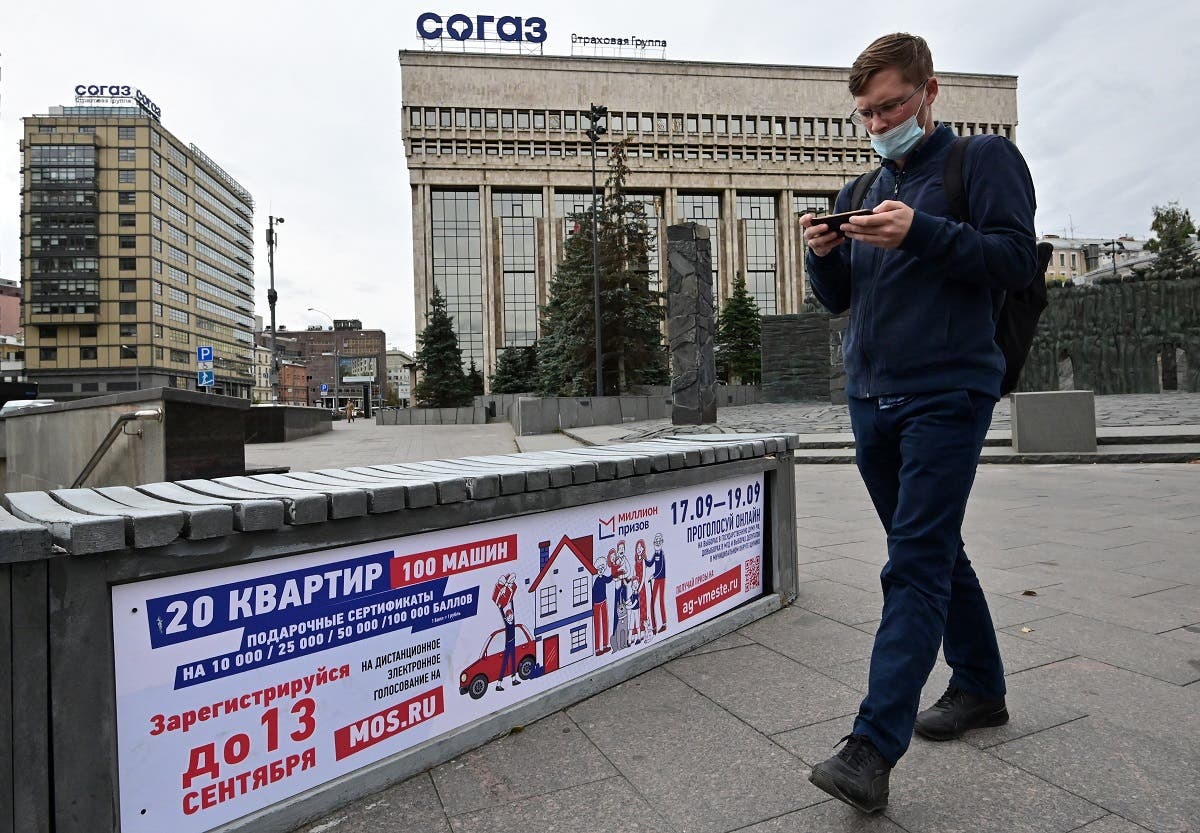 A man walks past a poster announcing the upcoming Russian parliamentary and local elections in Moscow on September 14, 2021. (Yuri Kadobnov/AFP)