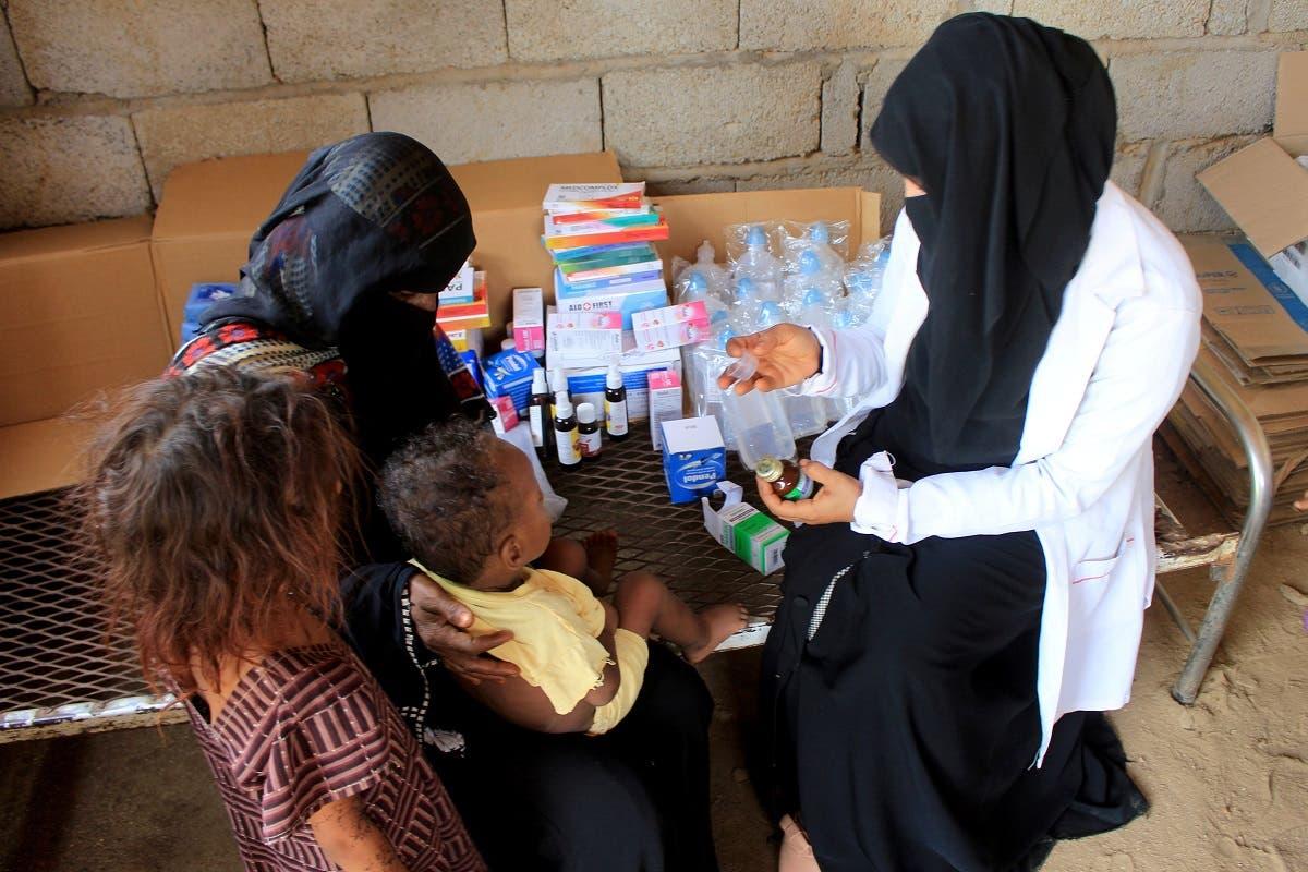 Volunteer health worker Ashwaq Mahmoud checks a medicine as she helps a child in Abs, Yemen September 13, 2021. Picture taken September 13, 2021. (Reuters)