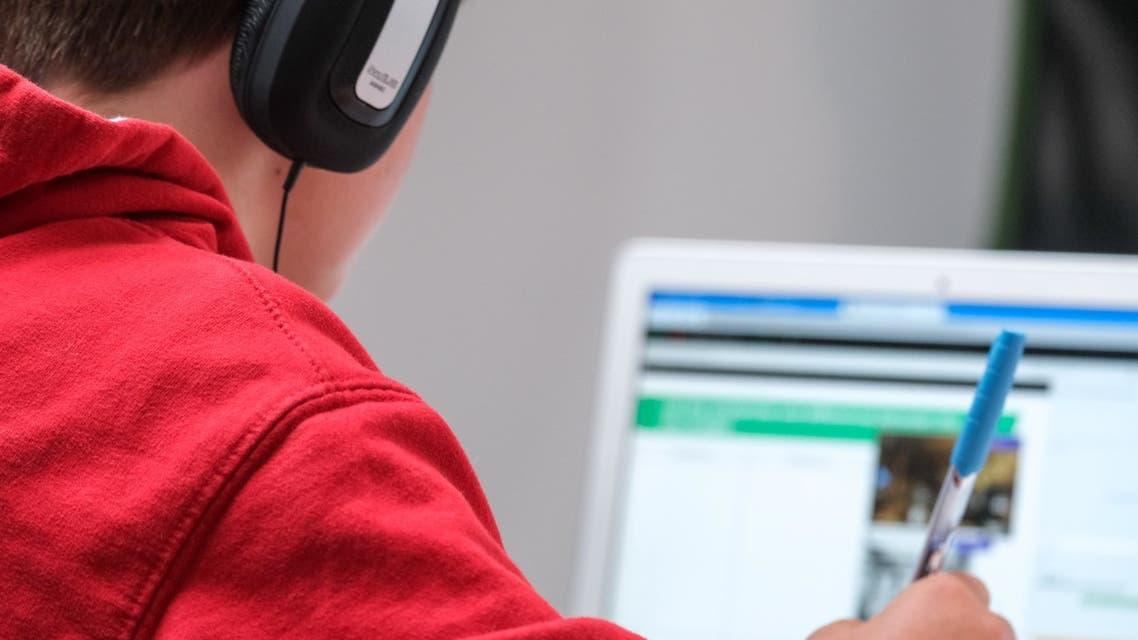Home schooling during lockdown, boy working on school work with laptop and headphones during coronavirus lockdown. (Unsplash, Compare Fibre)
