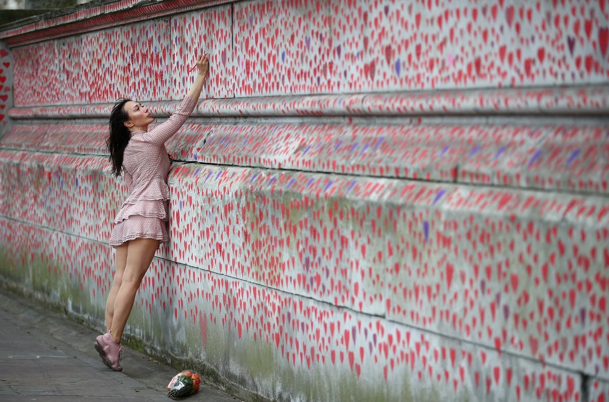 A woman paints on the National Covid Memorial wall beside St Thomas' hospital set as a memorial to all those who have died so far in the UK from the coronavirus disease (COVID-19), amid the coronavirus pandemic in London, Britain April 8, 2021. (Reuters)