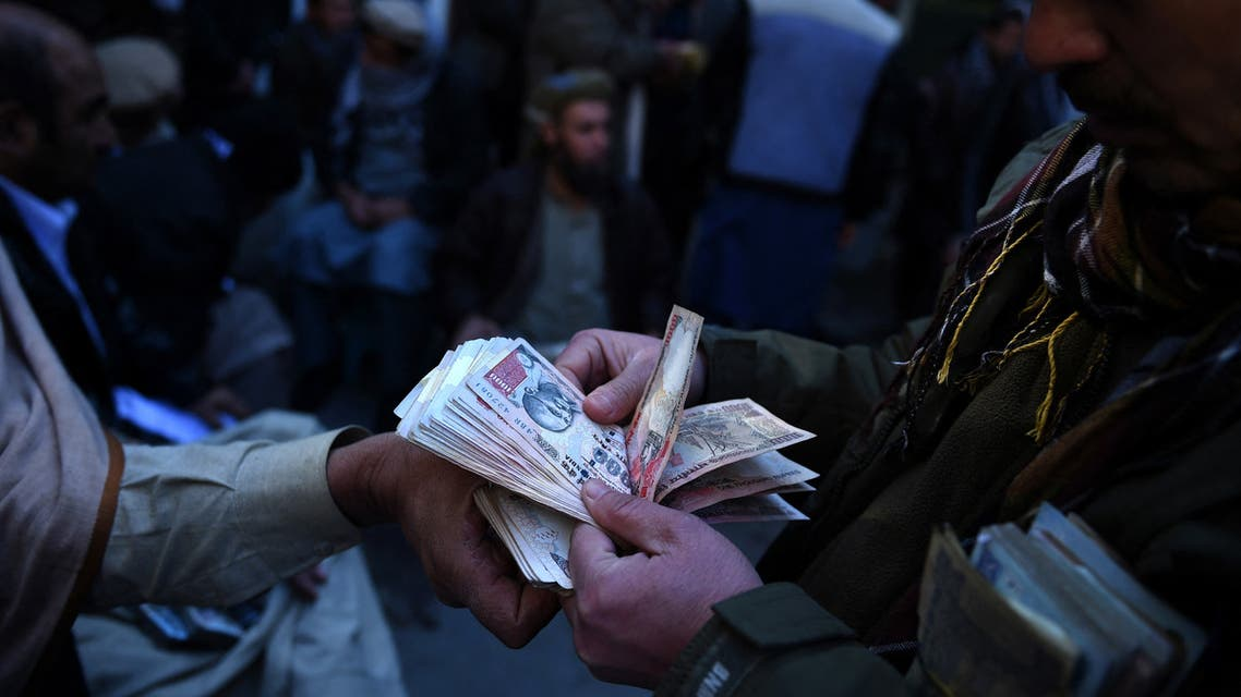 Afghan money changers count banknotes at the currency exchange Sarayee Shahzada market in Kabul on December 17, 2015.  (AFP)