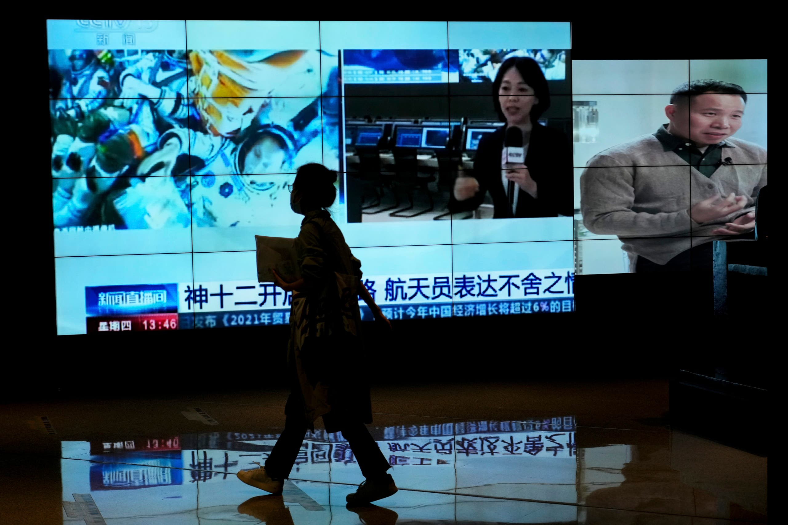 A woman walks by a TV screen showing CCTV broadcasting a news of Chinese astronauts sit inside the Shenzhou-12 manned spacecraft preparing to return to earth, at a shopping mall in Beijing. (File photo: AP)