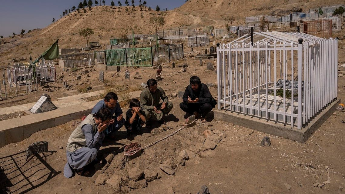 The Ahmadi family pray at the cemetery next to family graves of family members killed by a US drone strike, in Kabul, Sept. 13, 2021. (AP)