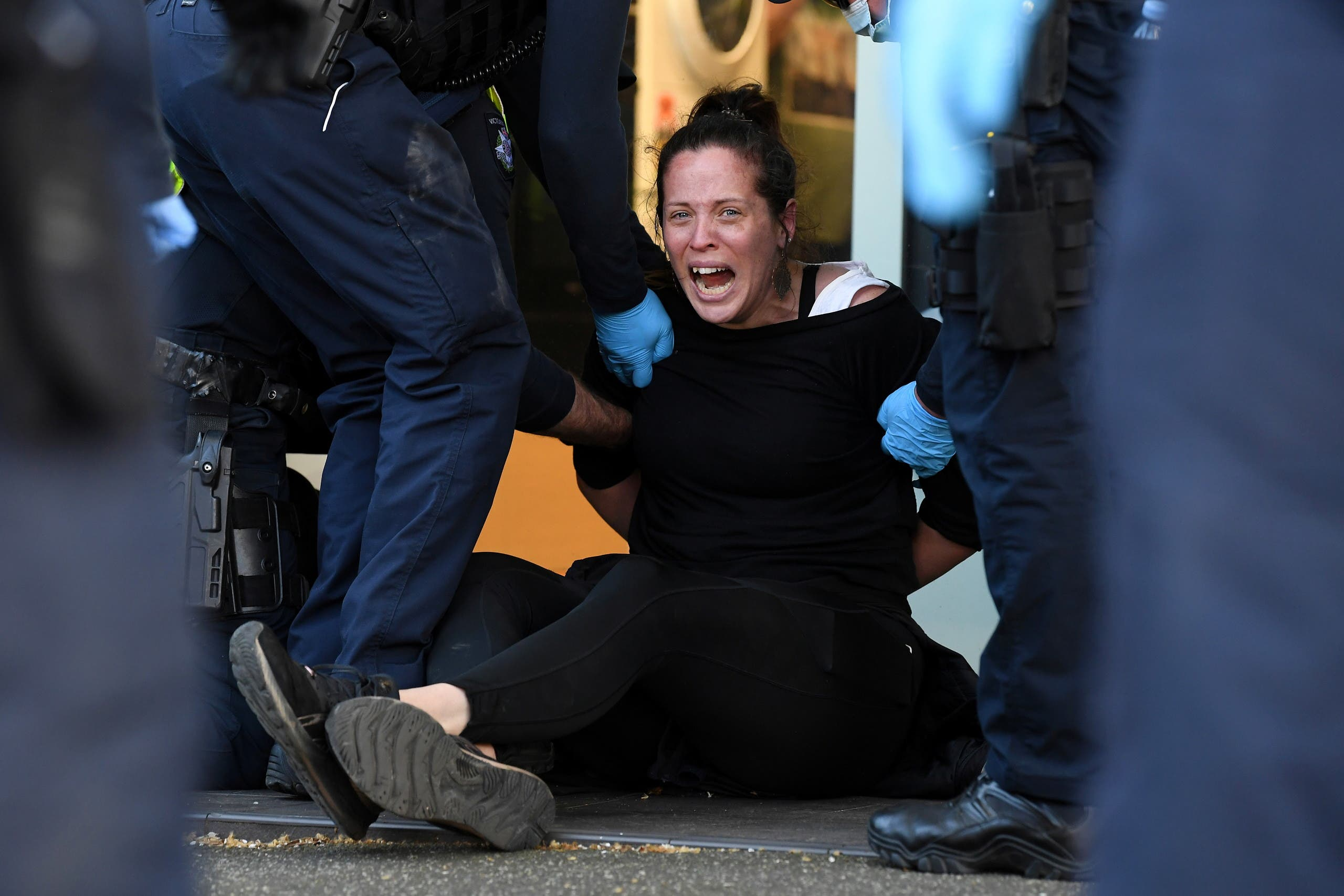 A protester is detained by Victoria police during a The Worldwide Rally for Freedom demonstration in Melbourne, Australia September 18, 2021. (Reuters)