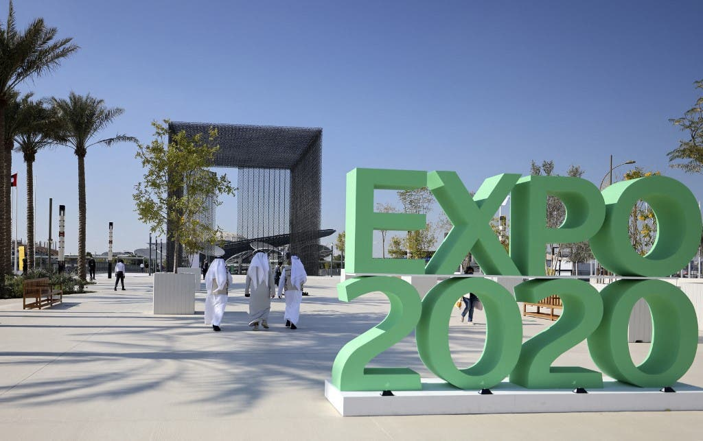 People walk past the official sign marking the Dubai Expo 2020 near the Sustainability Pavilion in Dubai on January 16, 2021. (AFP)