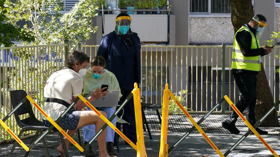 A health worker speaks with a member of the public at a coronavirus disease (COVID-19) vaccination clinic set up for residents of surrounding public housing towers in the Redfern suburb, where authorities are working to contain an emerging cluster of cases, as widespread lockdown continues in Sydney, Australia, September 17, 2021. (Reuters)