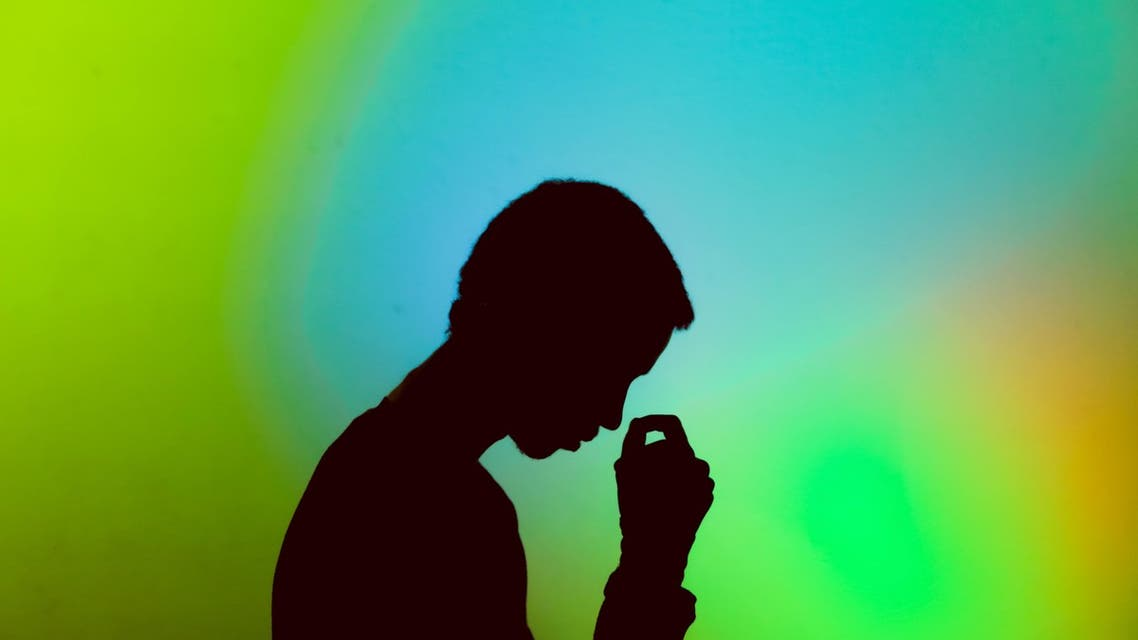 A man standing in front of a colorful background, thinking. (Unsplash, Gift Habeshaw)