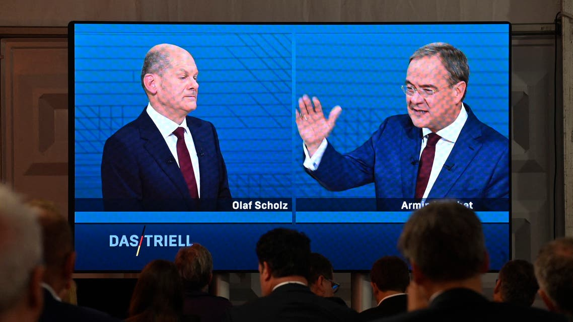 Journalists and party members watch on a screen from the press centre (L-R) Olaf Scholz, German Finance Minister, Vice-Chancellor and the Social Democrats (SPD) candidate for Chancellor and Armin Laschet, North Rhine-Westphalia's State Premier and the Christian Democratic Union (CDU) candidate for Chancellor as they attend an election TV debate in Berlin on September 12, 2021. (AFP)
