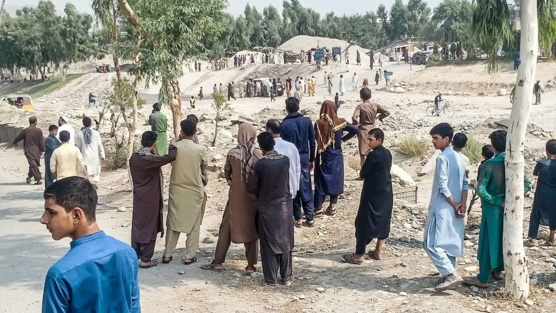 Taliban members and people gather at the site of a bomb explosion which targeted a pickup truck carrying Taliban fighters in Jalalabad on September 19, 2021, a day after at least two people were killed in a series of blasts in the area. (AFP)