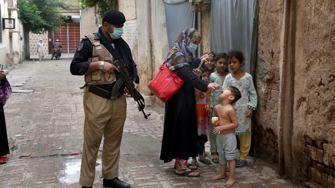 A police officer stands guard while a healthcare worker administers a polio vaccine to a child in Peshawar, Pakistan, Friday, July 30, 2021. (AP)