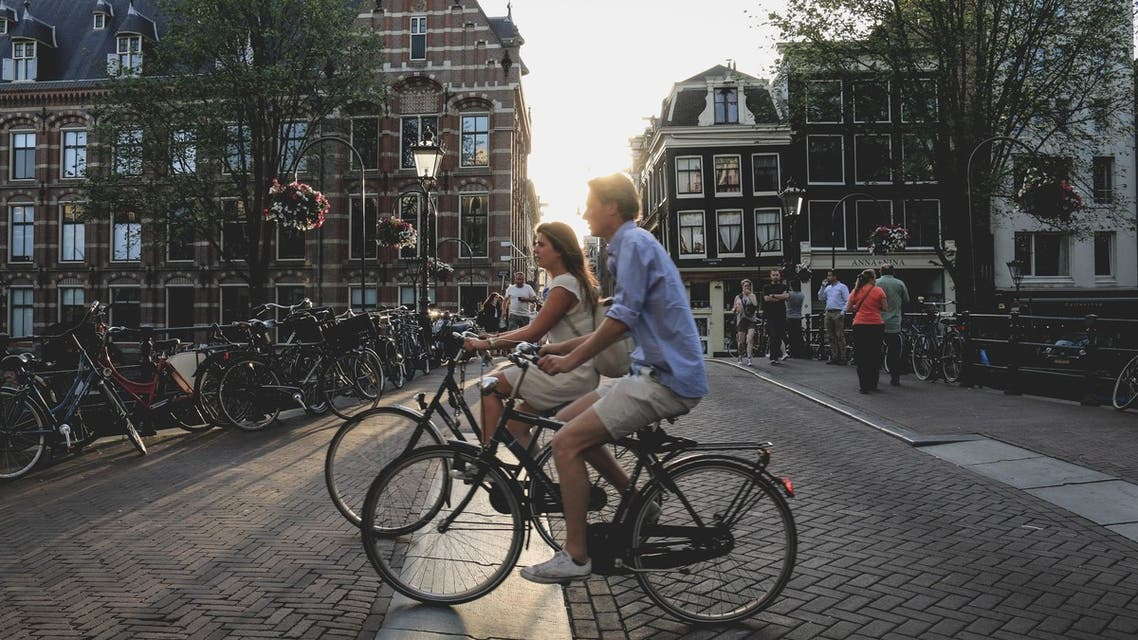 A man and woman cycling in Amsterdam, the Netherlands. (File photo: Unsplash, Sabina Fratila)