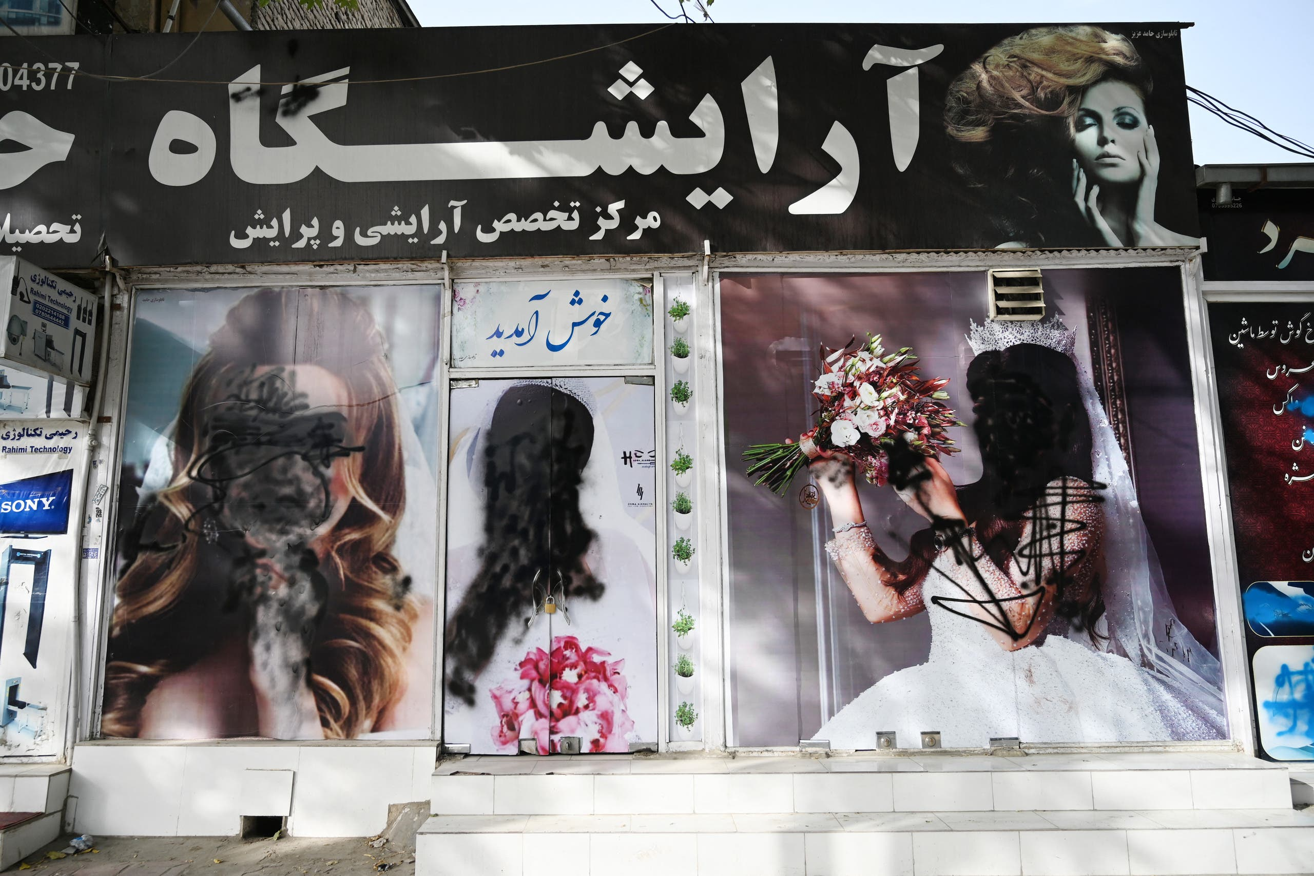 The facade of a beauty salon is pictured with images of women defaced using spray paint in Shar-e-Naw in Kabul on August 18, 2021. (AFP)
