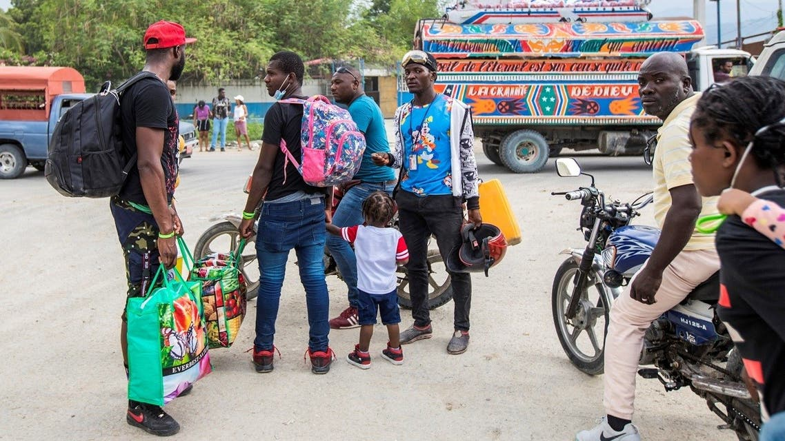 Haitian migrants who have just arrived after US authorities flew them out of a Texas border city on Sunday, hire moto taxis after leaving the airport, in Port-au-Prince, Haiti September 19, 2021. (Reuters/Ralph Tedy Erol)