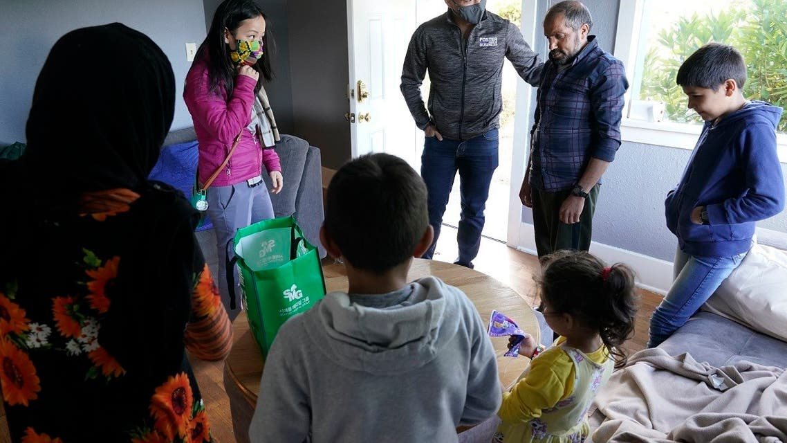 A Vietnamese-American family helps an Afghan family who fled, in Seattle, Sept. 20, 2021. (AP)