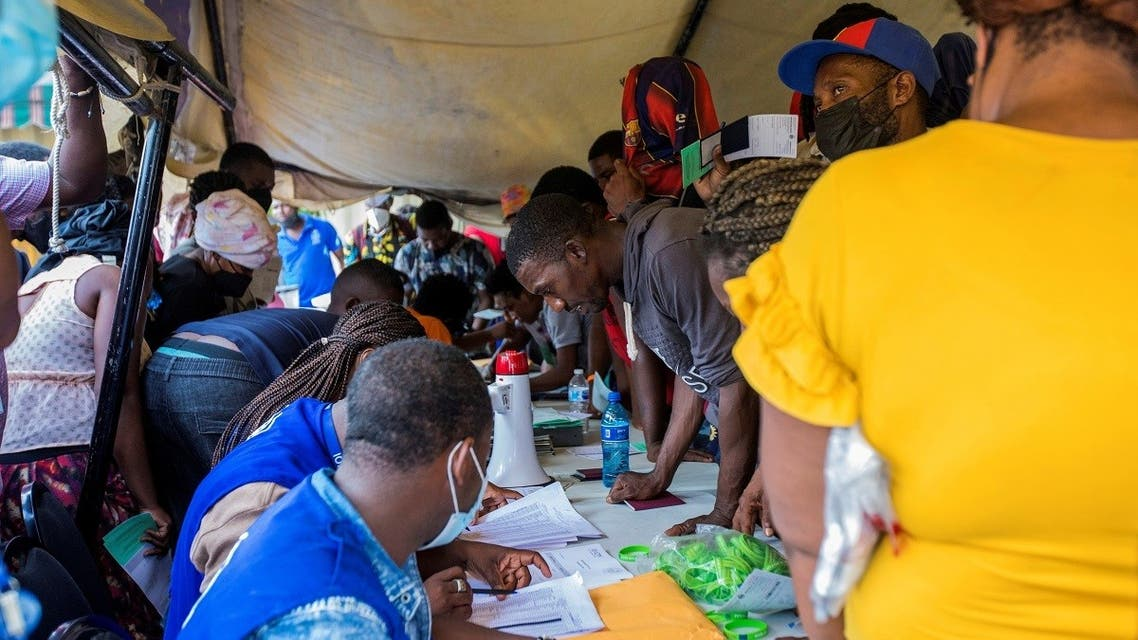 Haitian migrants gather under a tent to register with local immigration officials, after U.S. authorities flew them out of a Texas border city on Sunday where thousands of mostly Haitians had gathered under a bridge after crossing the Rio Grande river from Mexico, in Port-au-Prince, Haiti September 19, 2021. (Reuters)