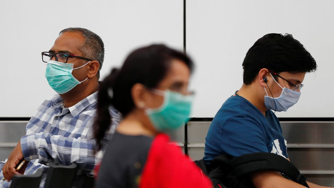 Passengers wearing protective masks sit at an airport terminal following an outbreak of the coronavirus disease (COVID-19), in New Delhi, India, March 14, 2020. (File photo: Reuters)