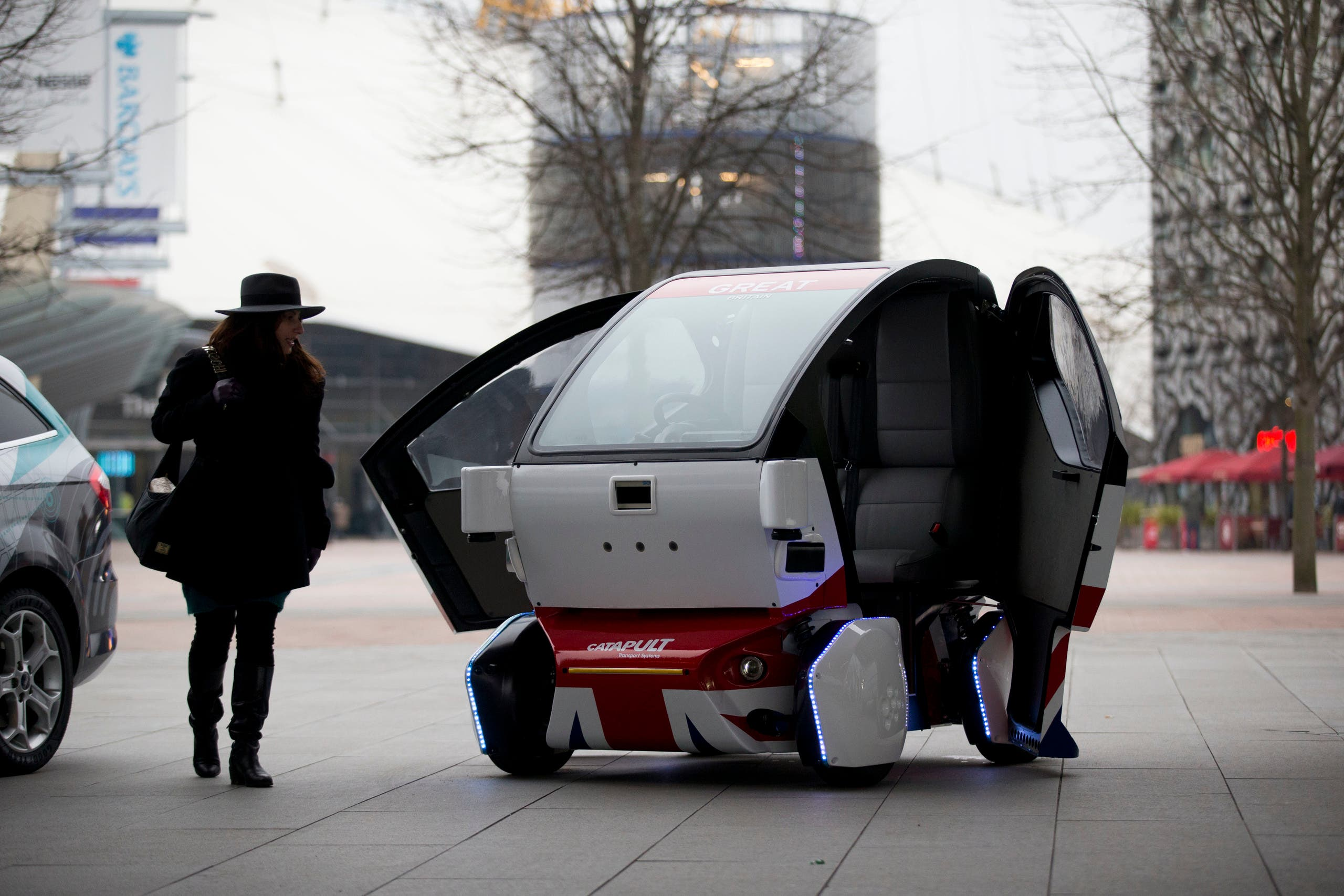A woman poses for photographers beside a prototype driverless car called a LUTZ (Low-carbon Urban Transport Zone) Pathfinder Pod during a launch event for the media. (File photo: AP)9973