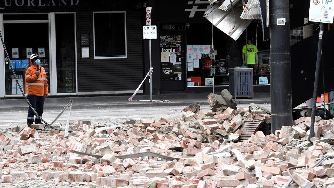 An emergency and rescue official examine the damage to a building in the popular shopping Chapel Street in Melbourne on September 22, 2021, after a 5.9 magnitude earthquake. (AFP)