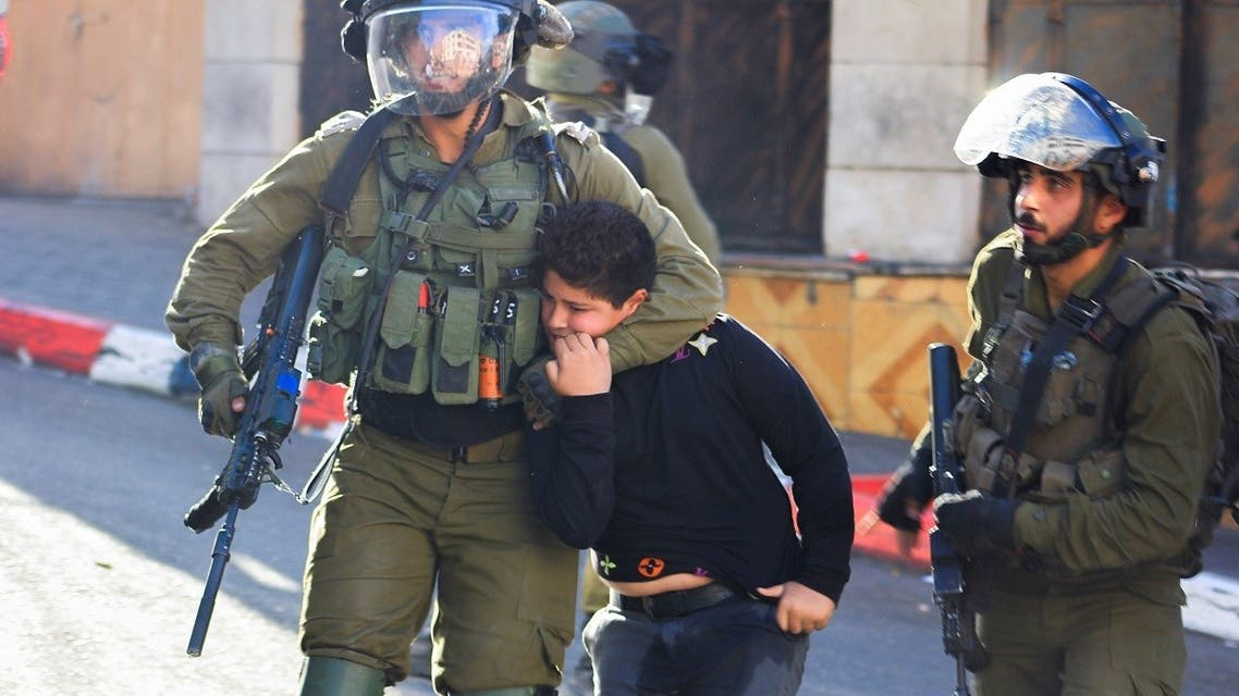 Israeli soldiers detain a Palestinian boy during clashes in Hebron, in the Israeli-occupied West Bank on September 23, 2021. (Reuters)