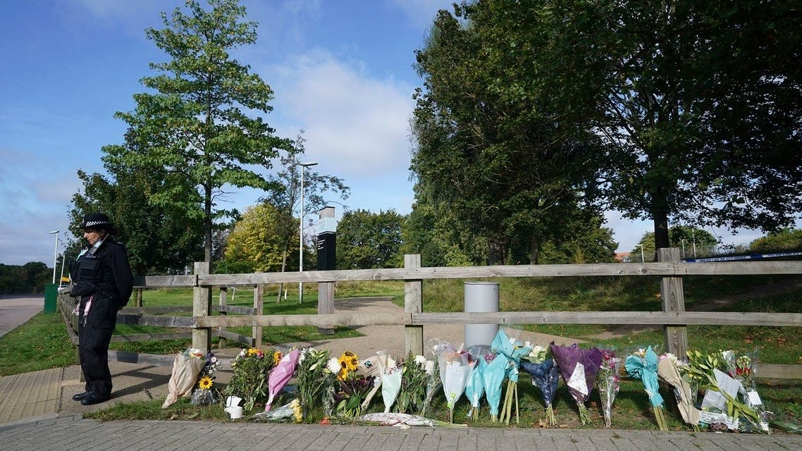 A police officer stands by floral tributes at Cator Park in Kidbrooke, near to the area where the body of Sabina Nessa was found, in London, on Sept. 23, 2021.  (AP)