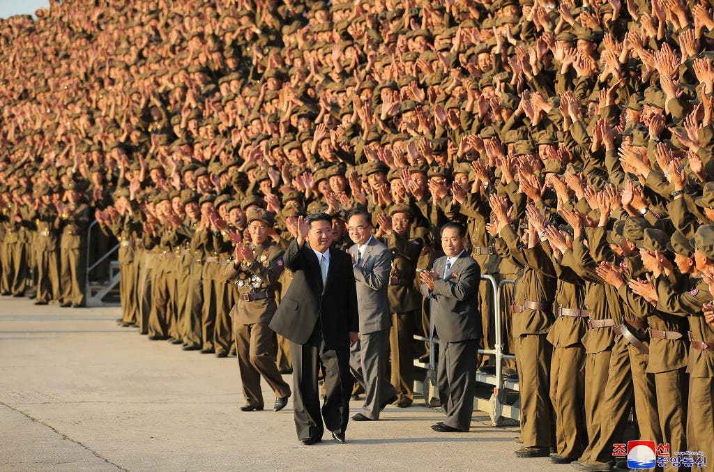 This picture taken on September 9, 2021 and released from North Korea's official Korean Central News Agency (KCNA) on September 10 shows North Korean leader Kim Jong Un (C) taking part in a photo session with participants in the military parade in Pyongyang. (AFP)