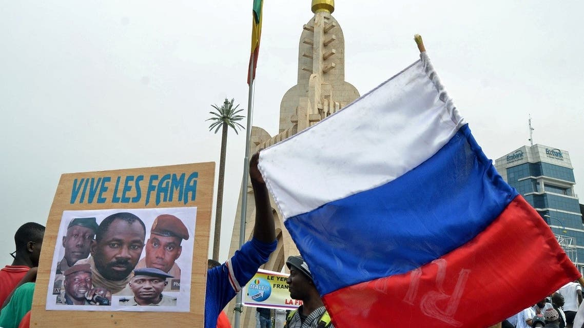 Malians holds a photograph with an image of coup leader Colonel Assimi Goita, who overthrew the president and prime minister this week, and Russia's flag during a pro-Malian Armed Forces (FAMA) demonstration in Bamako, Mali, May 28, 2021. (Reuters)