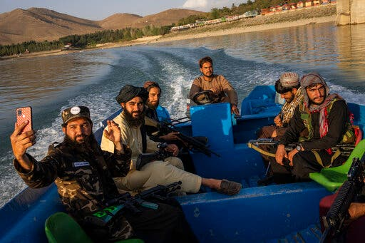 Taliban fighters enjoy a boat ride in the Qargha dam, outskirt of Kabul, Afghanistan, Sept. 24, 2021. (AP)