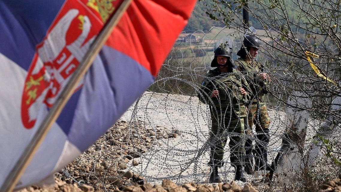 A Serbian flag is seen as the NATO Kosovo Force (KFOR) soldiers stand guard on a barricade at the border crossing Jarinje between Serbia and northern Kosovo on September 28, 2011. (AFP)