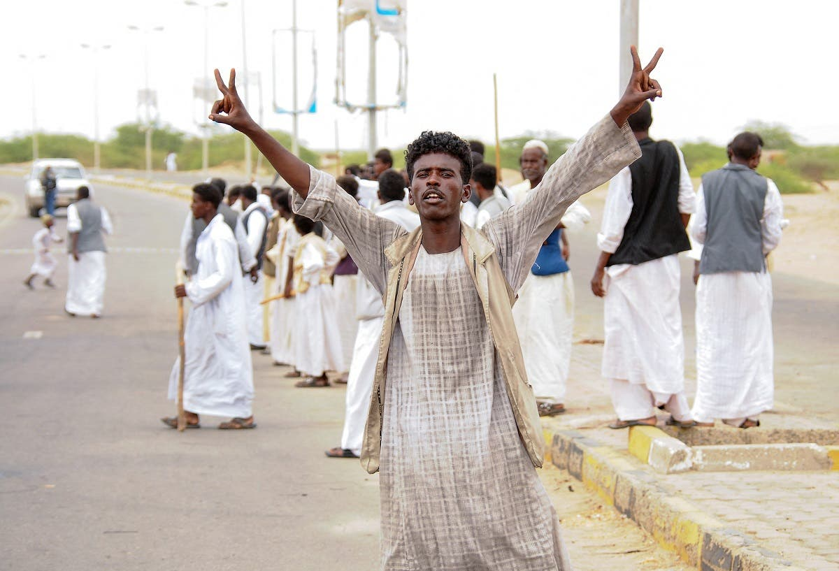 A protester flashes victory signs as supporters of Sudan's head of the Supreme Council of Beja Prefectures and Independent Umudiyyahs rally, following the arrival of a delegationg led by a member of the country's sovereign council in the city of Port Sudan, on September 26, 2021. (AFP)