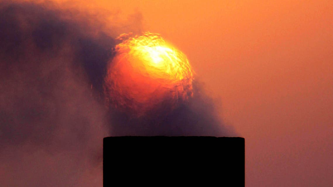 In this Wednesday, Sept. 9, 2009 file photo, smoke rises from an oil pipe at sunset in the desert oil field of Sakhir, Bahrain. (AP)