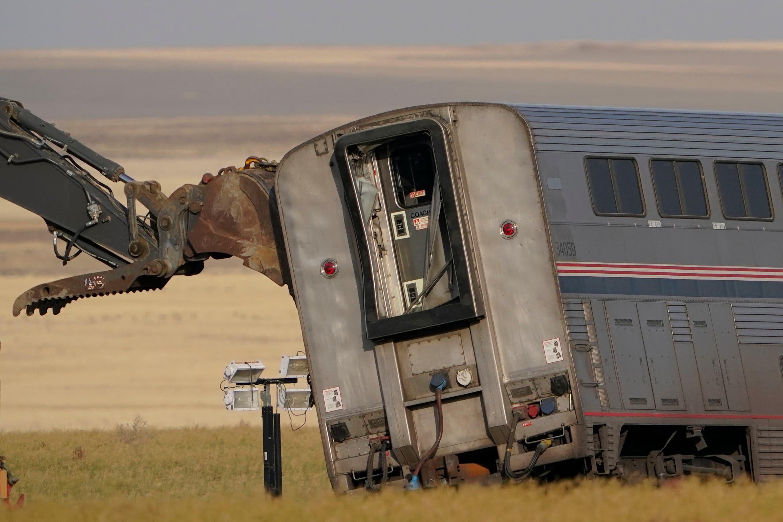A piece of heavy equipment props up a leaning train car, Sunday, Sept. 26, 2021, that was part of an Amtrak train that derailed Saturday, near Joplin, Montana. (AP)
