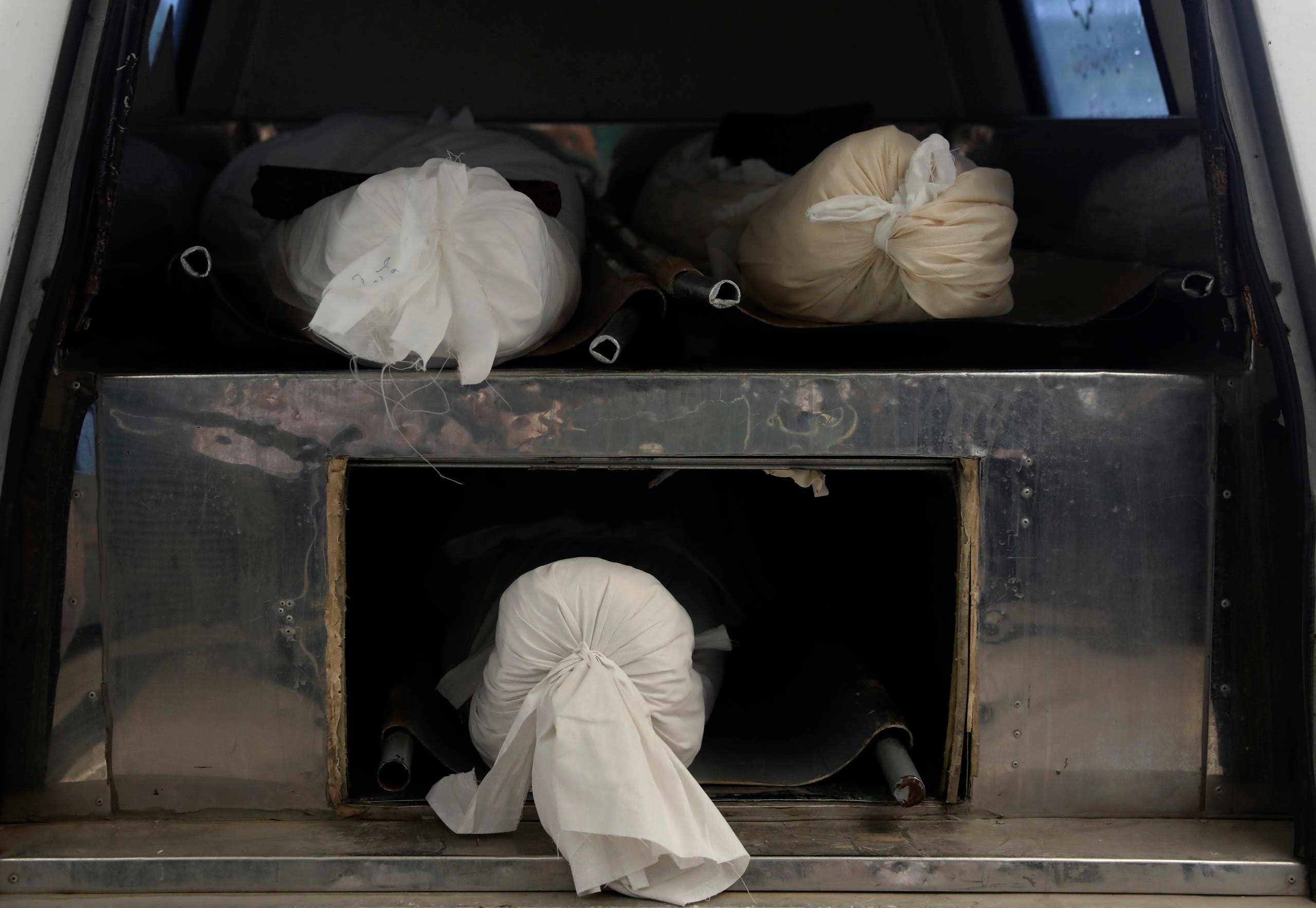 Bodies of a COVID-19 victims are shrouded and prepared to transfer for burial at Behesht-e-Masoumeh cemetery just outside the city of Qom, some 80 miles (125 kilometers) south of the capital Tehran, Iran, Wednesday, Sept. 15, 2021. (AP)