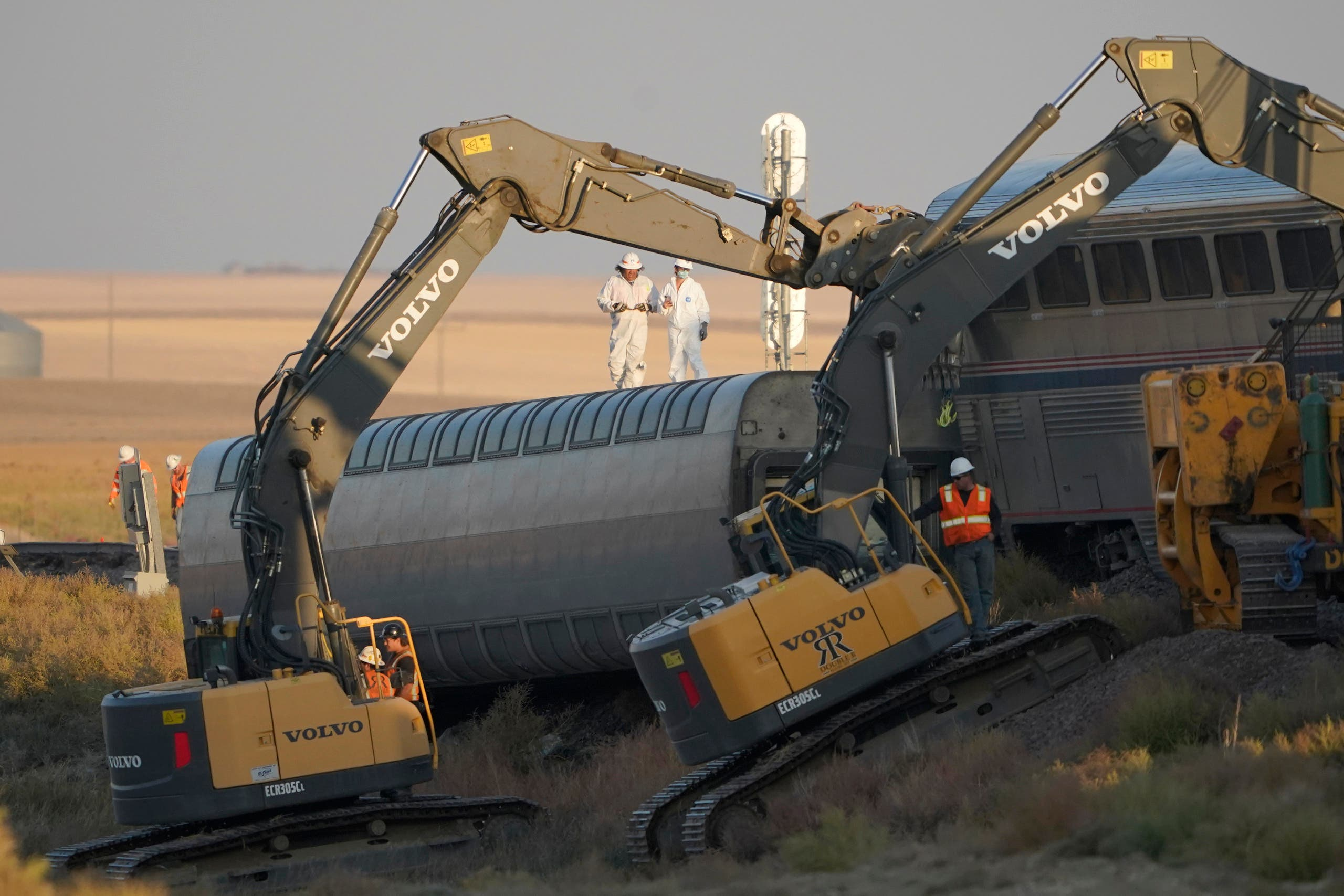 Workers stand on a train car on its side as front-loaders prop up another train car, Sunday, Sept. 26, 2021, from an Amtrak train that derailed Saturday, just west of Joplin, Mont. The westbound Empire Builder was en route to Seattle from Chicago with two locomotives and 10 cars. (AP)