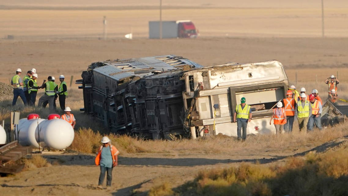 Workers stand Sunday, Sept. 26, 2021, near toppled cars from an Amtrak train that derailed Saturday, just west of Joplin, Mont. The westbound Empire Builder was en route to Seattle from Chicago with two locomotives and 10 cars. (AP)