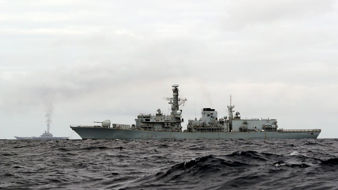 """This is a handout photo issued by Britain's Ministry of Defence taken on Wednesday Oct. 19, 2016, of HMS Richmond, foreground, a Type 23 Duke Class frigate, observing aircraft carrier Admiral Kuznetsov, at rear left, which is part of a Russian task group, during transit through the North Sea. Britain is sending warships to watch a Russian aircraft carrier group and other vessels as they sail through the North Sea and the English Channel. Defense Secretary Michael Fallon says that the military will watch the """"every step of the way.'' (PO(Phot) Dez Wade/MoD/Crown Copyright via AP)"""