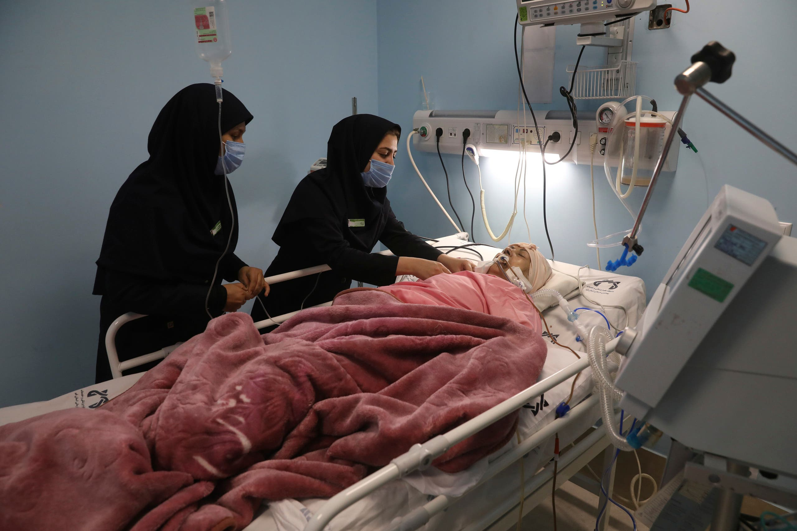 COVID-19 patient Marhamat Asadi, who is in a medically induced coma, is tended by nurses Fatemeh Najmeh Sadeghi, left, and Fereshteh Babakhanlou, at the COVID-19 ICU ward of Amir Al-Momenin hospital in the city of Qom, some 80 miles (125 kilometers) south of the capital Tehran, Iran, Wednesday, Sept. 15, 2021. (AP)